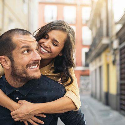 A woman hugs a man and he smiles at her over the shoulder. They're in Europe because they saved so much money with the Dental Savers Plan