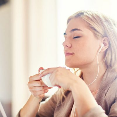 A woman sips a cup of coffee and listens to music through headphones, showing how calm she is at the dentist's office.