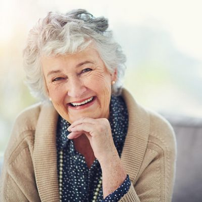 An older woman rests her head on her hand and smiles, showing off her beautiful dental implants.