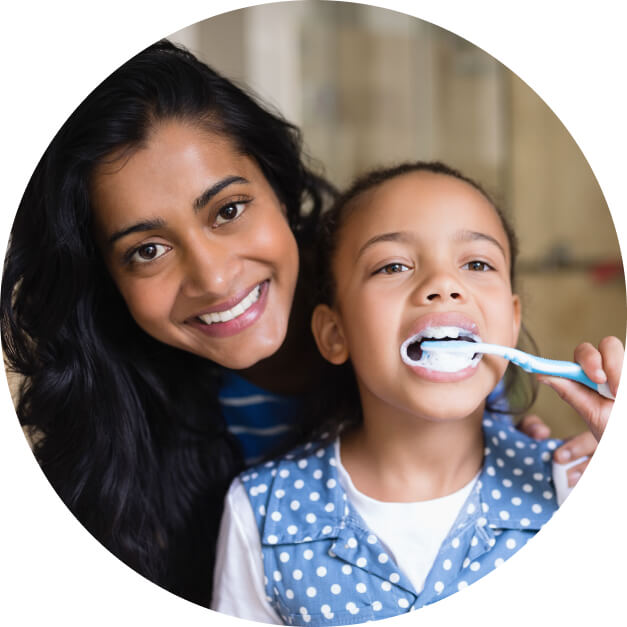 A woman smiles next to a young girl brushing her teeth during our family dentistry services.
