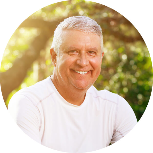 An older man with gray hair smiles, showing off his implants, one of our dental services.