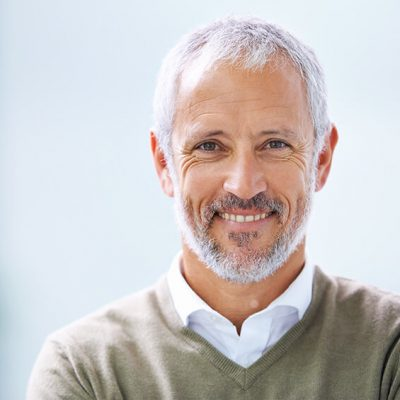 An older man with receding salt and pepper hair and beard smiles, showing off his stunning dental implants.