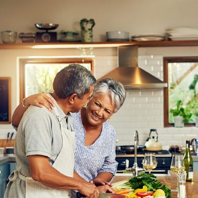 An older couple smiles in their modern kitchen while they chop vegetables they can eat because of restorative dentistry.