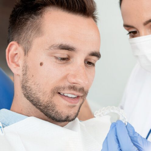 A young man looks at his Invisalign Clear Aligner in the dentist's chair