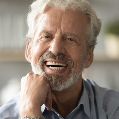 A smiling older man shows off his stunning dentures. He's got white hair and a partially white beard, and his dentures look amazing.
