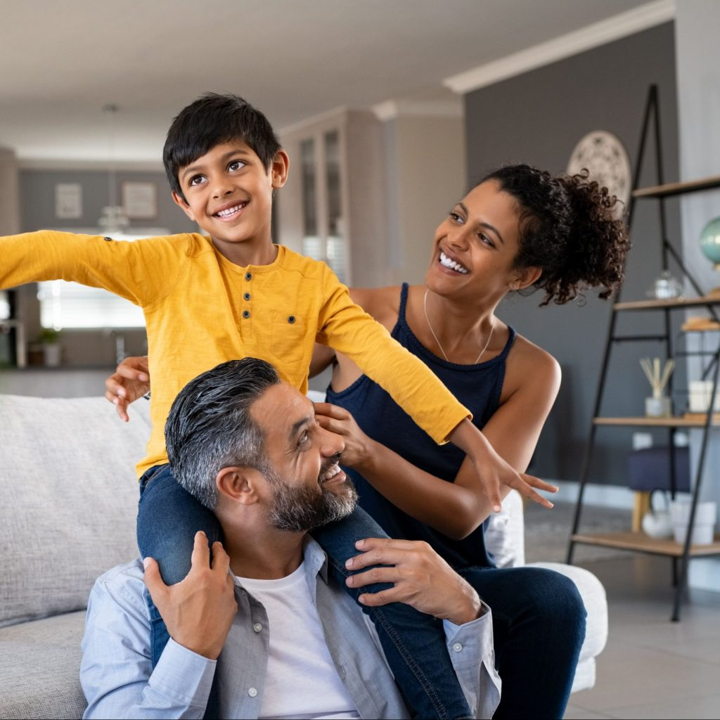 A family sits on their white couch at home, smiling with bright white teeth after visiting the dentist.